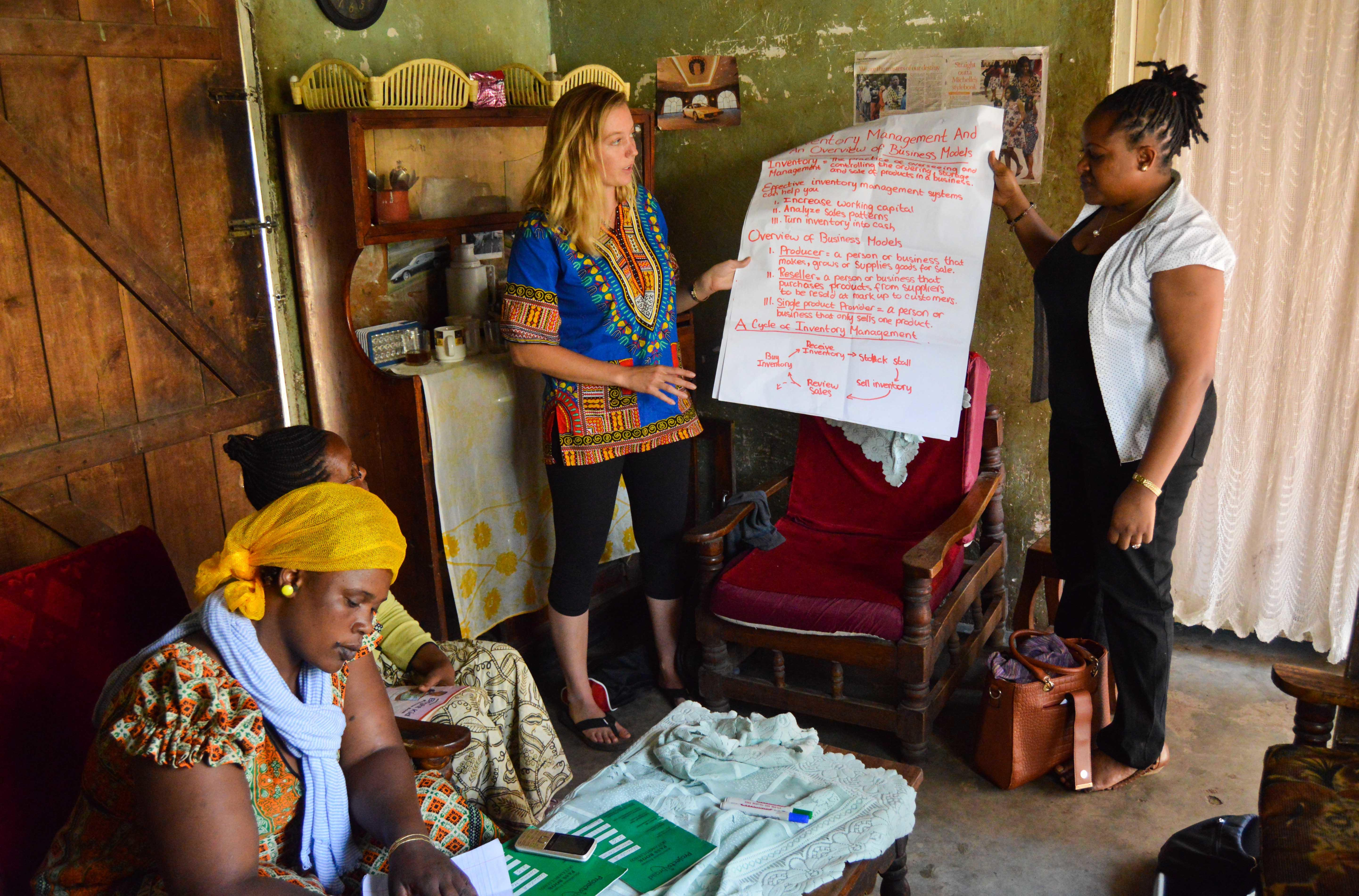 Interns gain micro-finance work experience in Tanzania by giving a presentation to small business owners